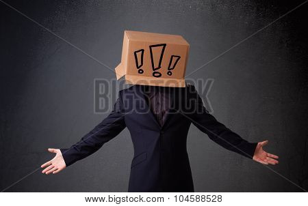 Young man standing and gesturing with a cardboard box on his head with exclamation point