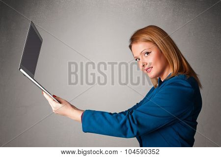 Pretty young woman holding modern laptot