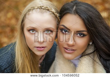 Close up portrait of two beautiful young girls on the background of autumn leaves