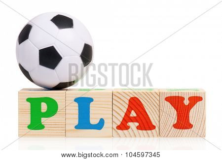 Wooden blocks arranged in the word PLAY and small soccer ball - isolated on white background