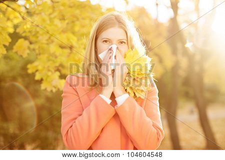 Girl with cold rhinitis on autumn background. Fall flu season. Ill sick sneezing woman. Handkerchief, vaccine against influenza virus Caught Cold Headache Allergy runny nose