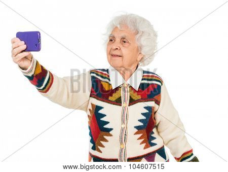 elderly woman taking selfie on a smartphone isolated on white background
