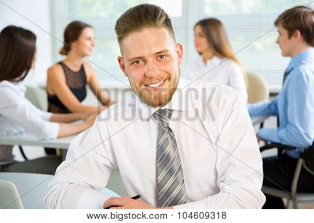 Young businessman with colleagues discussing in the background