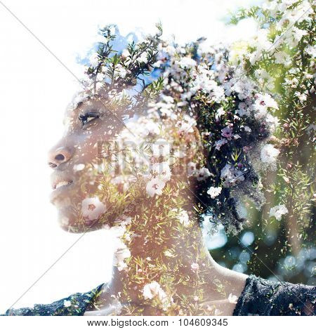 Double exposure portrait of attractive woman combined with photograph of tree