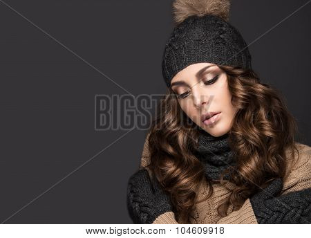 Beautiful girl with Smokeymakeup, curls in black knit hat. Warm winter image. Beauty face.