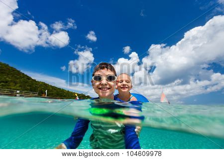 Split underwater photo of kids adorable little girl and cute boy splashing in a tropical ocean water during summer vacation
