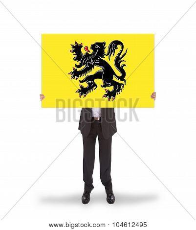Smiling Businessman Holding A Big Card, Flag Of Flanders