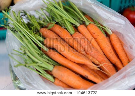sale, harvest, food, vegetables and agriculture concept - close up of carrot in plastic bag at street market