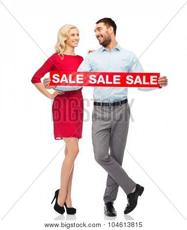 people, sale, discount and holidays concept - happy couple with red sale sign looking at each other