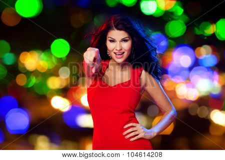 people, holidays, nightlife, gesture and leisure concept - beautiful sexy woman in red dress pointing finger on you at disco over night street lights background