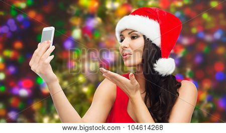 people, holidays, christmas and technology concept - beautiful sexy woman in red santa hat taking selfie picture by smartphone and sending blow kiss to camera