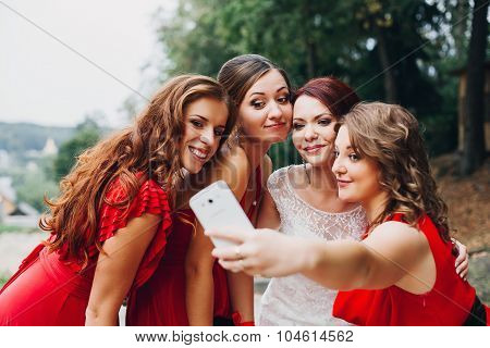 the bride and bridesmaids beautiful girls in red dresses doing selfie