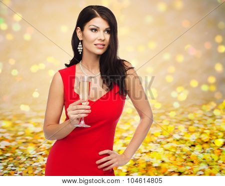people, holidays, christmas and celebration concept - beautiful sexy woman in red dress with champagne glass over golden glitter or lights background
