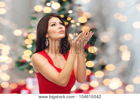 people, holidays and christmas concept - beautiful sexy woman in red dress making wish over lights background