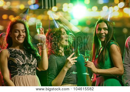 party, holidays, celebration, nightlife and people concept - happy female friends in party caps with glasses of non-alcoholic champagne dancing in night club