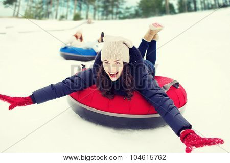 winter, leisure, sport, friendship and people concept - group of happy friends sliding down on snow tubes