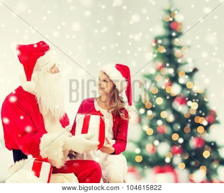 holidays, childhood and people concept - smiling little girl, santa claus with gifts over living room, christmas tree and snow background