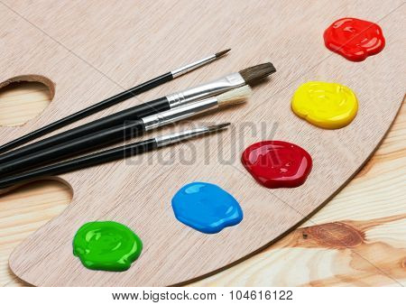 Wooden art palette with paints and brushes, on wooden background