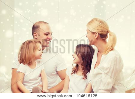 family, childhood, communication, people and home concept - smiling parents with two little girls talking at home