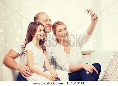 family, home, technology and people - happy family with camera taking picture over snowflakes background