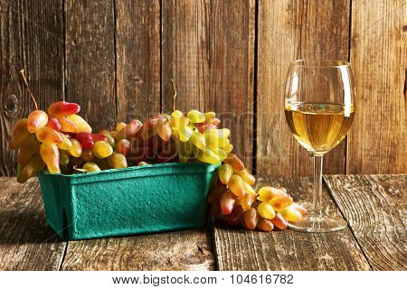 Fresh grapes and white wine on old wooden table