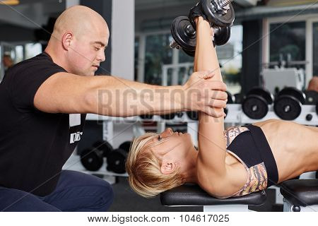 Personal Trainer Helping Blonde Woman In Press Of Dumbbells