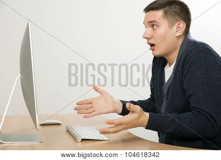 Young man expresses shock looking on large computer screen