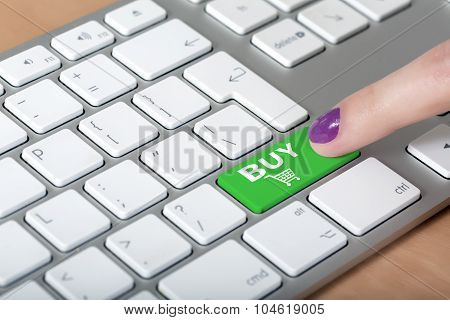 Female finger clicking on BUY button on computer keyboard
