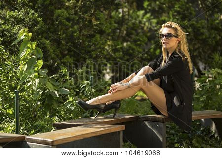 Striking blond woman in sunglasses sitting on a Park bench.