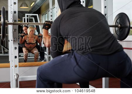 Personal Trainer Helping Blonde Woman In Squats