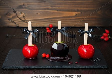 Three black and red poison caramel apples. Traditional dessert recipe for Halloween party. Selective