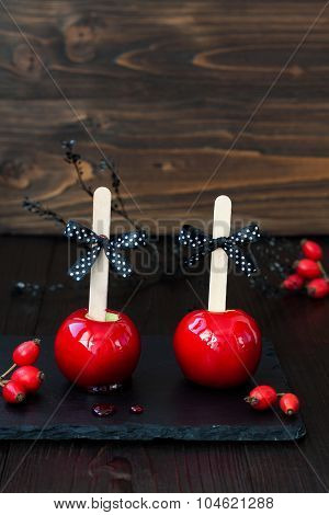 Two red caramel apples. Traditional dessert recipe for Halloween party. Selective focus.