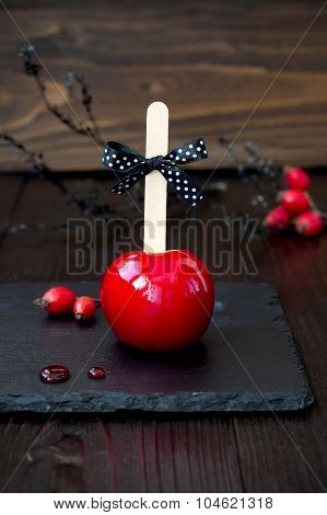 Red caramel apple. Close up. Traditional dessert recipe for Halloween party. Selective focus.