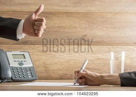 Businessman Expressing His Approval By Making A Thumbs Up Gesture Over A Contract Being Signed
