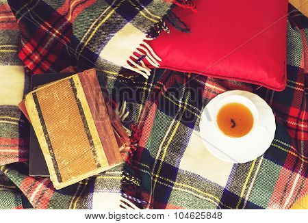 Woolen plaid cup of tea old books red pillow on wooden background. Top view. Toned