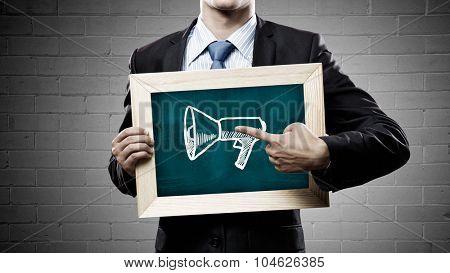 Unrecognizable businessman holding chalkboard with adverisement concept