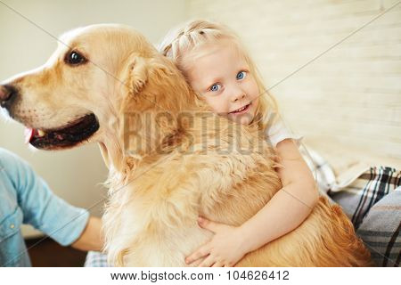 Adorable little girl embracing fluffy pet and looking at camera