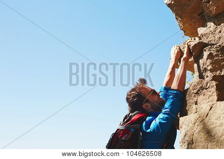 Active young sportsman climbing on top of rock