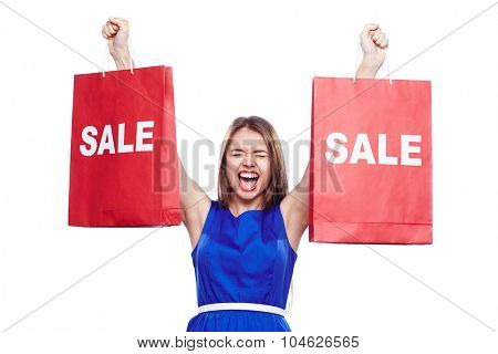 Young woman expressing gladness while holding paperbags in raised hands
