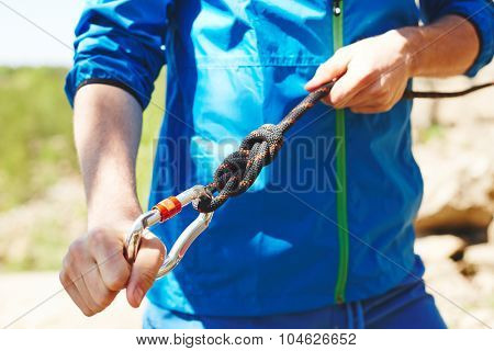 Sportsman preparing carabiner for climbing
