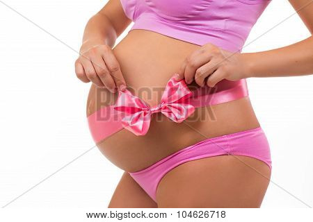 Close Portrait Of A Pregnant Belly With Pink Satin Bow Isolated On White Background. Horizontal