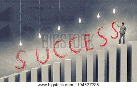 Back view of businessman on bars writing word success
