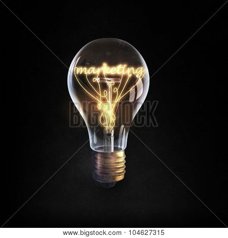 Glowing glass light bulb with marketing word inside