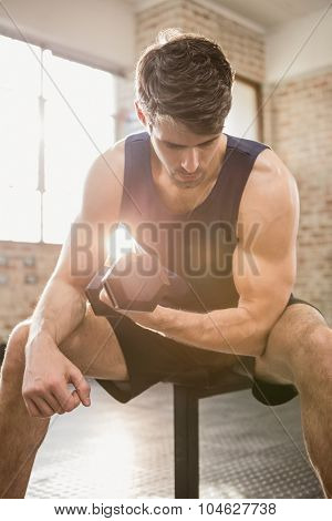 Man lifting dumbbell while sitting at the gym