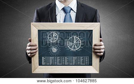 Unrecognizable businessman holding chalkboard with metal market graphs