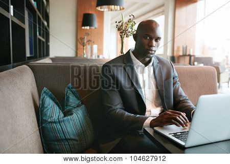 African Businessman Working On Laptop In Coffee Shop