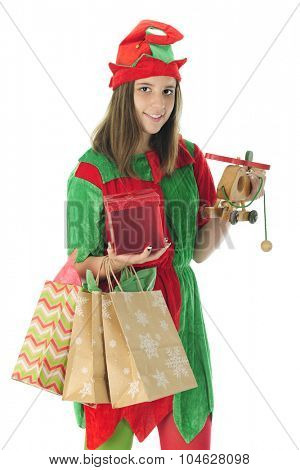 A pretty teen elf smiling at the viewer as she carries gift bags, a wrapped box and a toy helicopter in preparation for Christmas.  On a white background.