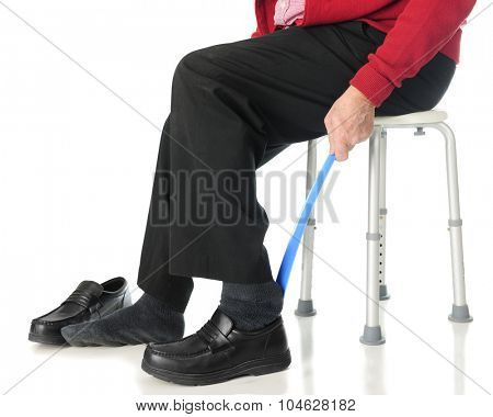 Close-up view of a senior man sliding into his loafers with the aid of a long-handled shoe horn.  On a white background.