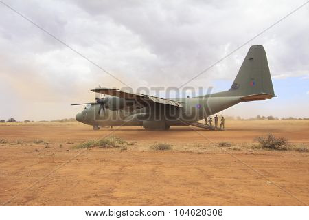 NANYUKI, KENYA - CIRCA OCTOBER 2015 - British RAF Hercules aircraft lands on field airstrip during training exercise with British Army. Government spending cuts will reduce future training like this.