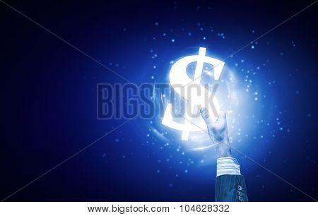 Close up of human hand holding dollar symbol on blue background